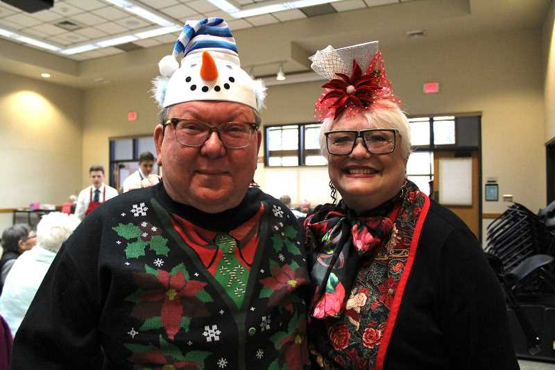 SPOKESMAN PHOTO: SAM STITES - Frank Rine and Donna Atkinson pose for a photo at the Wilsonville Community Centers holiday luncheon Friday, Dec. 15. Rine was one of six winners of the ugly sweater contest.
