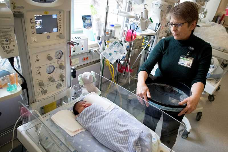 PAMPLIN MEDIA GROUP PHOTO: JAIME VALDEZ - Laura Beer, director and associate professor of music therapy at Marylhurst University, sings to Jose Ochoa-Ramirez, a 6-day-old preemie in the Neonatal Intensive Care Unit at Oregon Health & Science University.