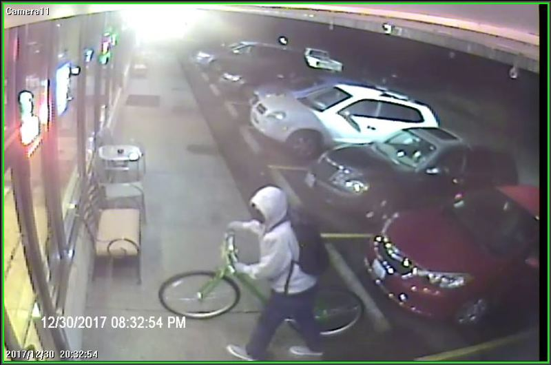 PHOTO COURTESY: OCPD - The suspect is seen on surveillance camera arriving on a bicycle to the Lucky Rooster Coffee Shop.