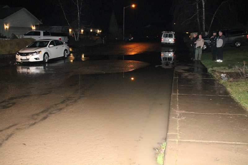 PIONEER PHOTO: CONNER WILLIAMS - An eight-inch water main that ruptured on Thursday night in Molalla caused 19 homes to be without water until about 5 a.m. the next day. In this photo, the water drains as maintenance crews work the scene.