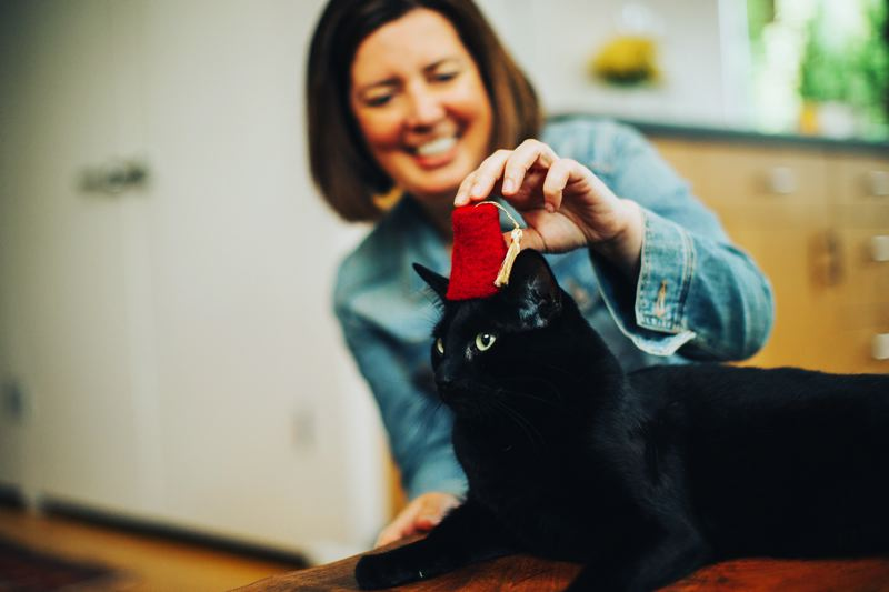 PHOTOS: COURTESY THE GRAND POOBOX - An interior designer for Cushman & Wakefield by day, Karsted here relaxes after hours her friend's cat Zeus. (Her own cat, not pictured, is called Rex.)
