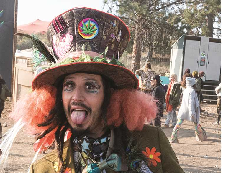 LON AUSTIN/CENTRAL OREGONIAN - A Symbiosis eclipse festival visitor dressed as the Mad Hatter poses for a photo.