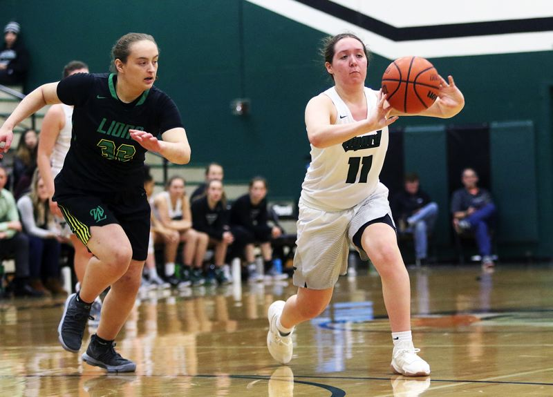 DAN BROOD - Tigard junior Paige LaFountain (right) passes the ball as West Linn senior Lizzy Harrick closes in.
