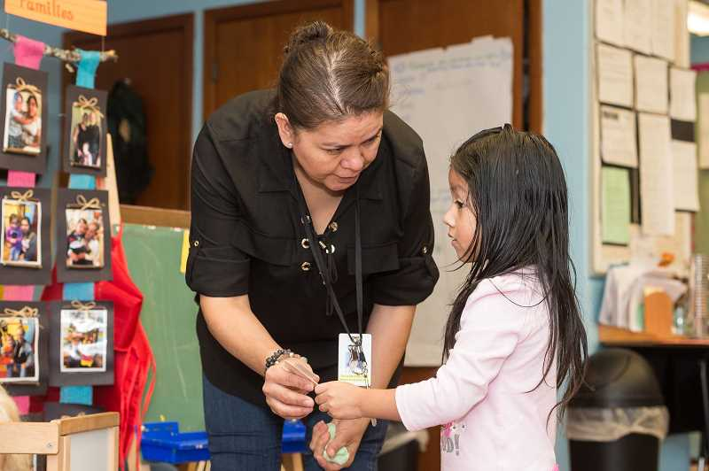 HILLSBORO TRIBUNE PHOTO: CHRISTOPHER OERTELL - Teacher assistant Silvia Barraza helps Annelise Luna at Reedville Elementary in Hillsboro, Ore., on Dec. 4, 2017