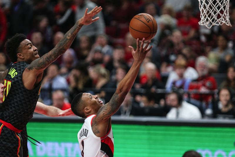 TRIBUNE PHOTO: DAVID BLAIR - Damian Lillard (right) drives for a layup against Atlanta as the Trail Blazers roll past the Hawks on Friday night at Moda Center.