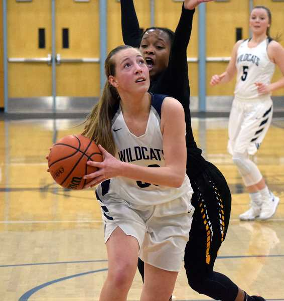 SPOKESMAN PHOTO: TANNER RUSS - Wilsonville sophomore Kayla Hieb works her way towards the basket past Milwaukie defenders on Jan. 5.