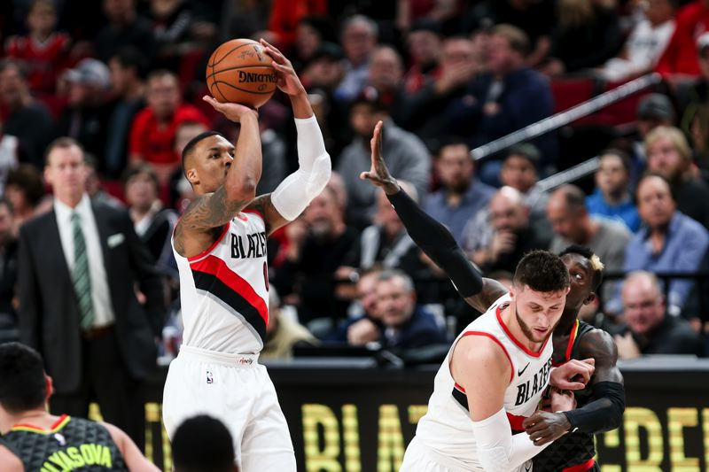 TRIBUNE PHOTO: DAVID BLAIR - Blazers center Jusuf Nurkic (right) helps guard Damian Lillard get space for a jump shot on Friday as Portland defeats Atlanta, 110-89, at Moda Center.