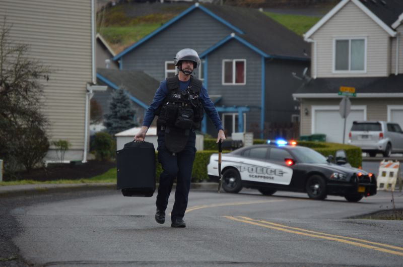 SPOTLIGHT PHOTO: NICOLE THILL - Sgt. Steve Collins, an explosive disposal officer with the Portland Police Bureau Bomb Squad walks back towards his vehicle after removing what appeared to be a small explosvie device on EM Watts Road Monday morning,  Jan. 8.  Scappoose Police Department was alerted to the object when a passerby saw it Monday morning.