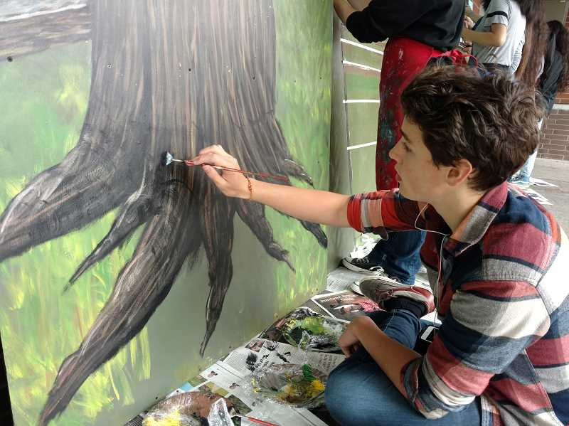 SUBMITTED PHOTO - Sophomore Jared Wieland paints tree roots on the mural.