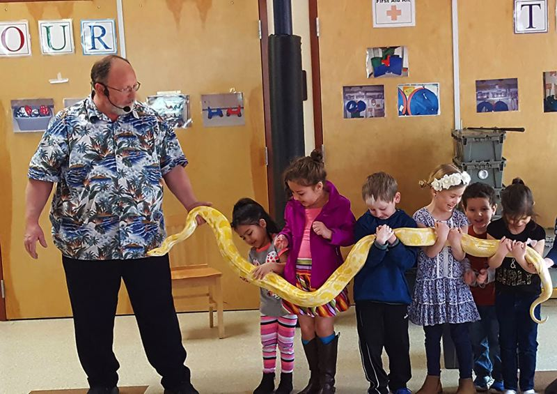 PHOTO BY: LESLIE ROBINETTE - Gladstone kindergarten students get acquainted with a boa constrictor during their weekly science lesson at the Gladstone Center for Children and Families. The school is focused on the unique needs of the districts youngest students, with on-site family services provided by 10 agencies.