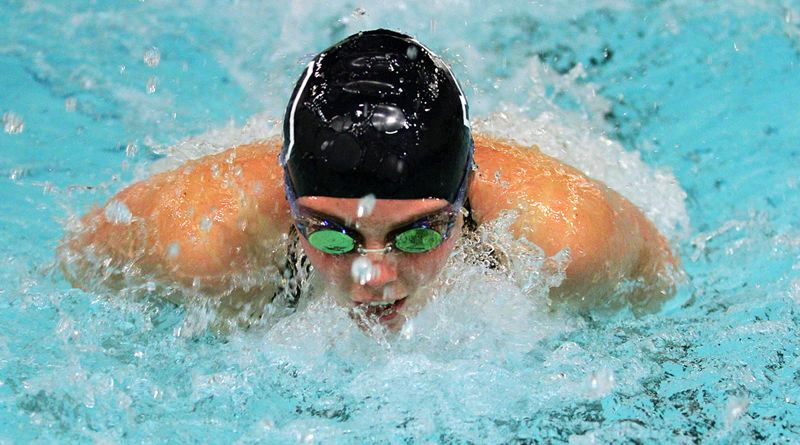 REVIEW PHOTO: MILES VANCE - Lake Oswego junior Grace Marshall breaks the surface of the water during her win in the 100-yard butterfly against Sherwood at Lake Oswego District Pool on Jan. 4.