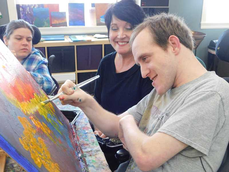 ESTACADA NEWS PHOTO: EMILY LINDSTRAND - Mike Marble works with Infusion Gallery Art Director Parris Foley on a painting. Marble is one of several attendees of Infusion Gallery to have work featured in the Spiral Gallerys student art show.