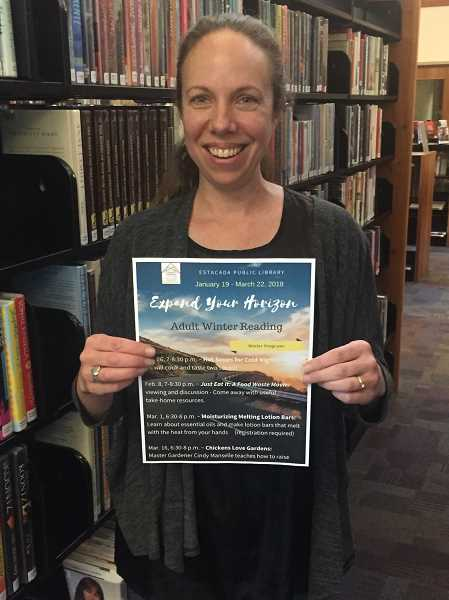 ESTACADA NEWS PHOTO: EMILY LINDSTRAND - Estacada Adult Services Librarian Leslie Pearson holds the flyer for this year's Adult Winter Reading program at the library.