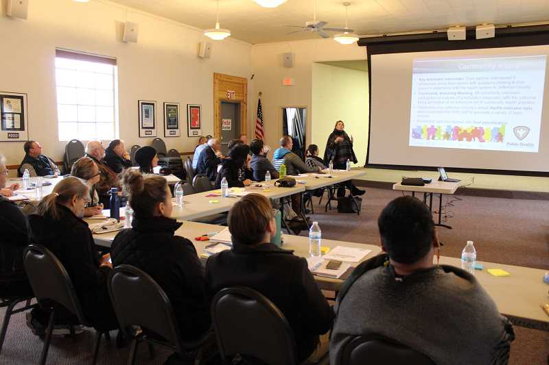HOLLY M. GILL - Beth Ann Beamer, of Jefferson County Public Health, standing at center back, gives a presentation on the history of the Community Health Improvement Plan.