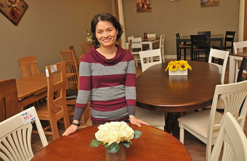 STAFF PHOTOS: VERN UYETAKE  - Kim Thuy Duong, who owns TriThi Company with her husband, Trinh Huu Bui, stands by some of the tables the company imports from Viet Nam. The tables are all made of high quality hardwoods grown in the United States and Asia.