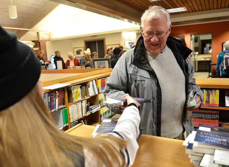 REVIEW PHOTO: VERN UYETAKE - Louis Barker of Lake Oswego picks up his free copy of 'Good Morning, Midnight' at the Lake Oswego Public Library on Monday.