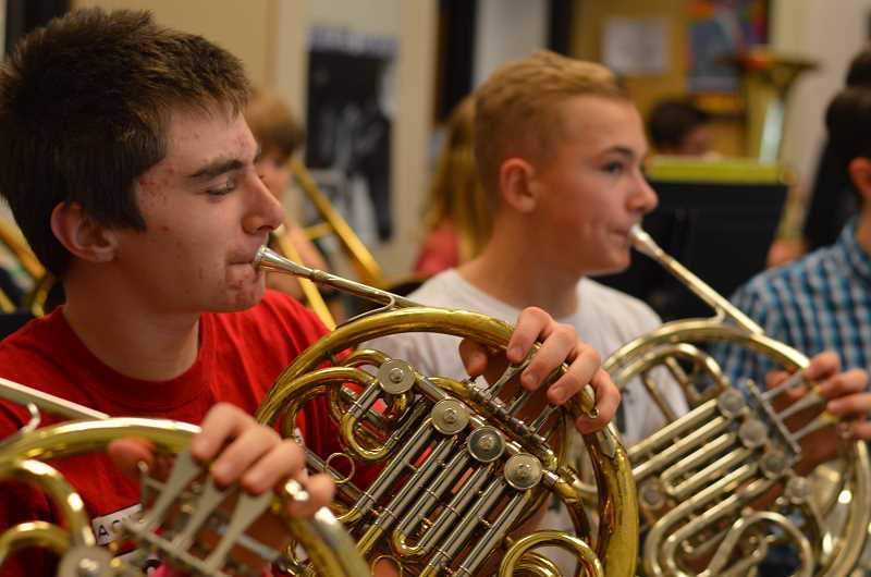 TIDINGS PHOTO: CLARA HOWELL  - Eighth-graders Luke Hashbarger (left) and Ian Hansen (right) play the horn during band practice.
