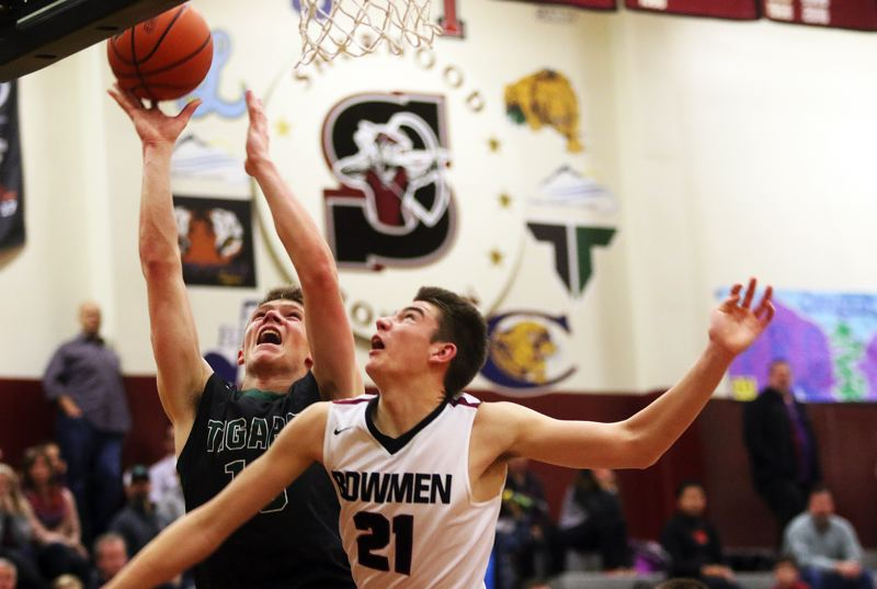 DAN BROOD - Tigard High School senior post Austin Dufort (left) goes up to the basket against Sherwood junior Braden Thorn during Friday's Three Rivers League contest.