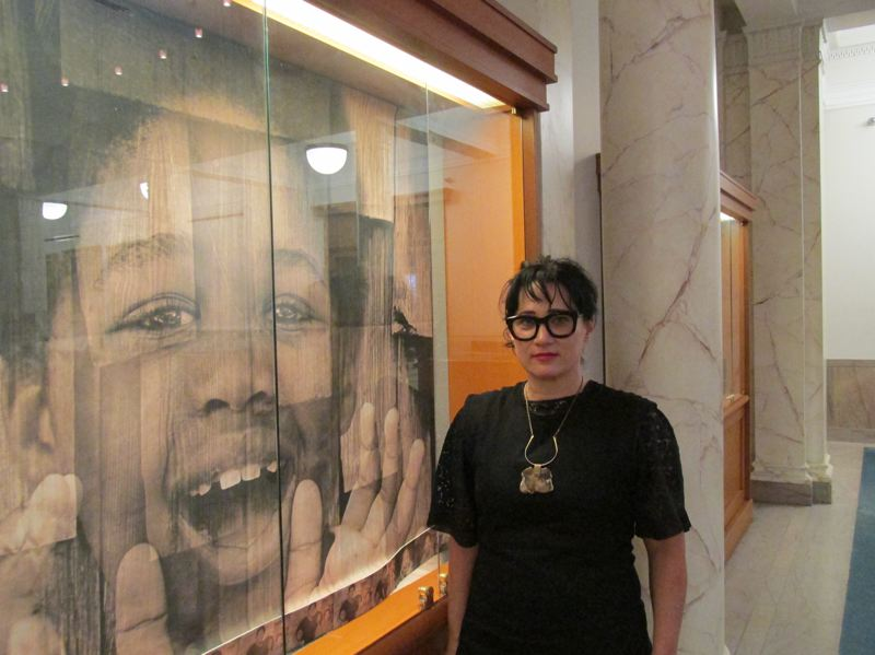 OUTLOOK PHOTO: TERESA CARSON - Photographer Rachel ORourke stands by one of the portraits of a child living in Greshams Human Solutions Family Shelter.