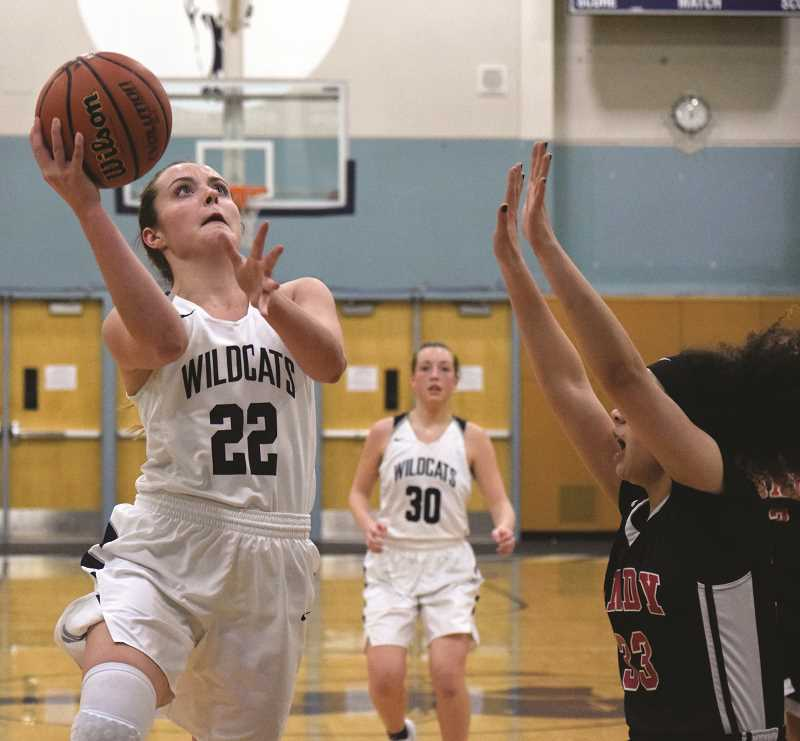 SPOKESMAN PHOTO: TANNER RUSS - Junior Cydney Gutridge gets to the rim for a layup against a Sandy defender. The Wildcats defeated Sandy 80-25 on Friday, Jan. 12.