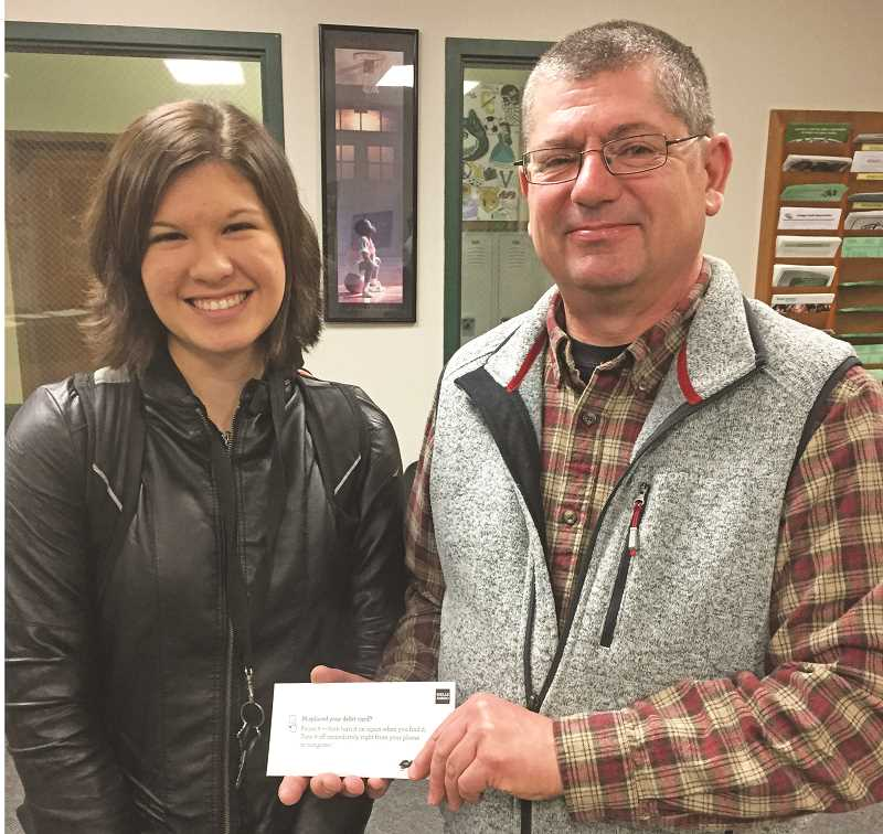 COURTESY PHOTO: ROBERT PRINSLOW - Robert Prinslow, president of Love Santa, Inc., accepts a check for $875.64 from North Marion High School senior Melinda Chappell, who spearheaded fundraising efforts during the Christmas season.