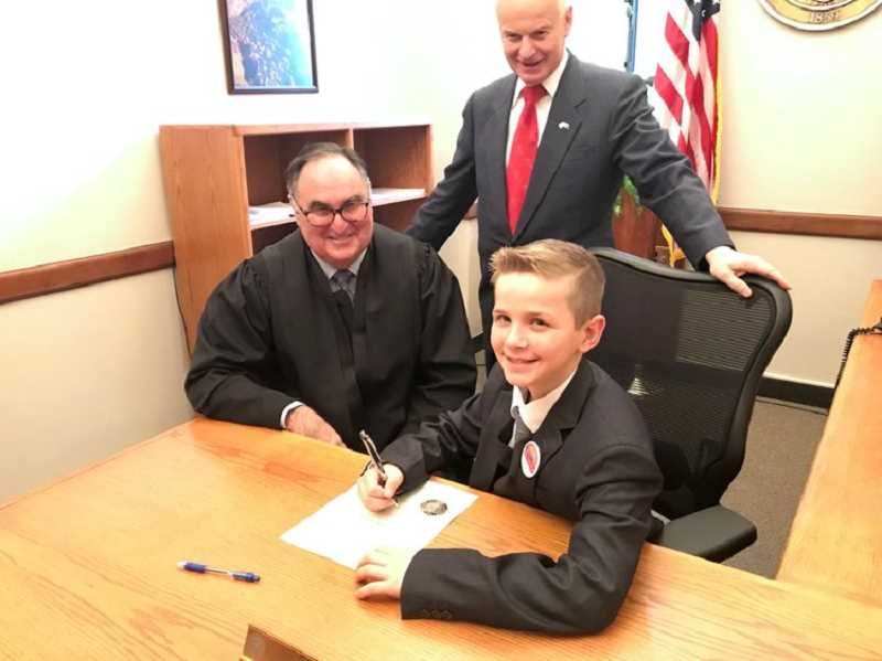 COURTESY PHOTO: SECRETARY OF STATE'S OFFICE - Oregon's first Kid Governor Dom Peters (right), a fifth-grader from Gervais, signed his official oath of office Jan. 8. He is pictured with Secretary of State Dennis Richardson (center) and former Oregon Supreme Court Chief Justice Paul De Muniz.