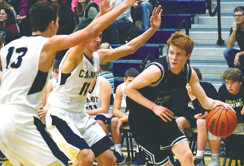 TANNER RUSS - CANBY HERALD - Newberg senior Ben O'Loughlin drives the baseline during the Tigers' 48-43 road win over Canby. O'Loughlin scored eight points to help NHS claim its first league win of the season.