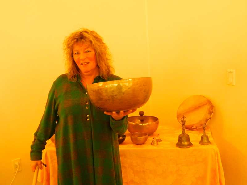 ESTACADA NEWS PHOTO: EMILY LINDSTRAND - Lauri Shainsky smiles while she holds one of her singing bowls. Shainsky uses the bowls to conduct sound healing in her Eagle Creek studio.