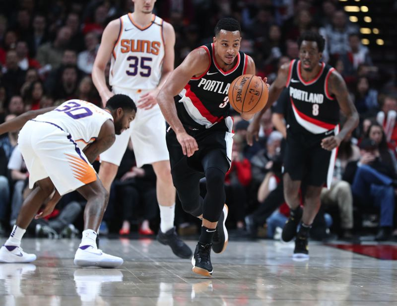 TRIBUNE PHOTO: JAIME VALDEZ - Trail Blazers guard CJ McCollum takes off with the ball after making a steal off Troy Daniels (left) of the Phoenix Suns.
