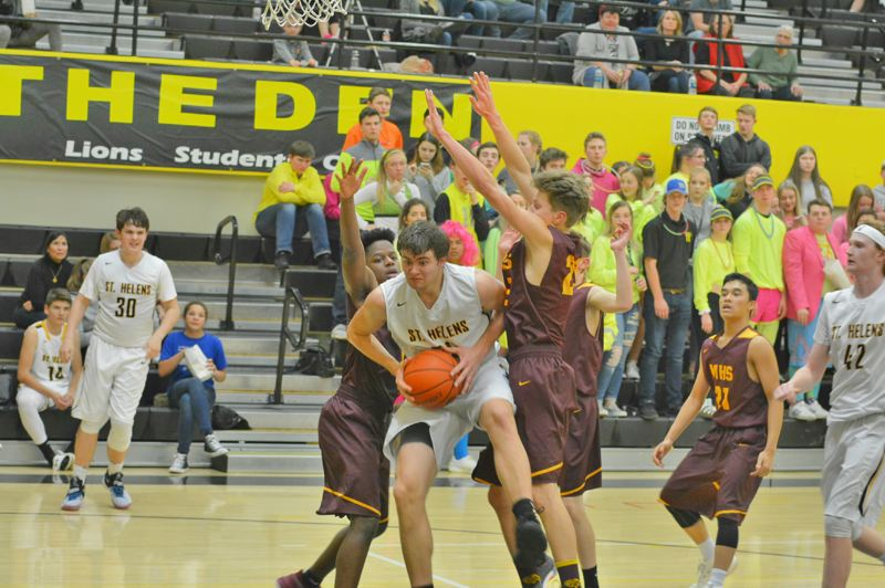 SPOTLIGHT PHOTO: JAKE MCNEAL - Lions senior forward Jacob Falk, center, goes up through Milwaukie seniors Marcel Nemarundwe, left, and Dylan Stradley, right, Tuesday in St. Helens.