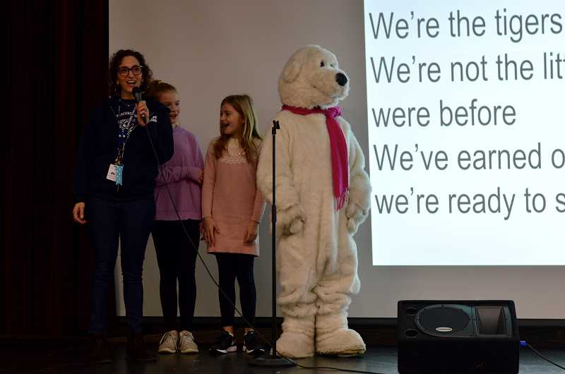 TIDINGS PHOTO: CLARA HOWELL  - Instructional Coordinator Meg Leonard, left, Karli Sanders and Simone Del Carlo sing the Stafford song with the Polar Plunge bear during a morning assembly regarding Oregon Special Olympics and the Polar Plunge team.