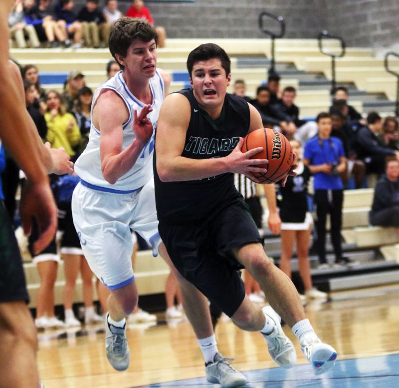 DAN BROOD - Tigard's Jake Leavitt (right) looks to drive to the basket in the win over Lakeridge.