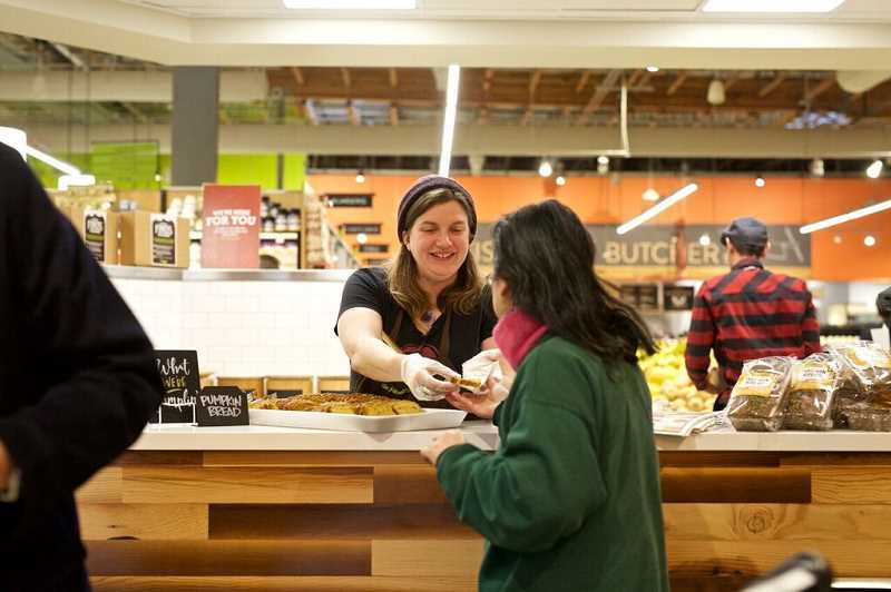 An unidentified New Seasons Market employee serves a customer a sample from the bakery. New Seasons recently began offering eligible employees paid parental leave.