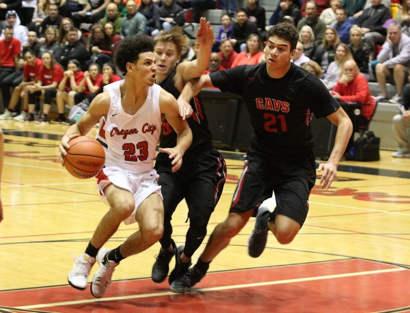 REVIEW/NEWS PHOTO: JIM BESEDA - Oregon City's Teron Bradford (23) takes the ball to the basket under pressure from Clackamas' Bubba Jaha (5) and Cole Turner (21) in the final seconds of Tuesday's game at Oregon City