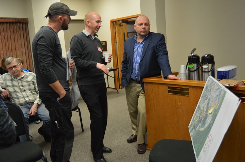 SPOTLIGHT PHOTO: NICOLE THILL - Consultant Matt Bell, center, speaks with Peter Luciano, a St. Helens resident, and Scot Stockwell, the St. Helens School District superintendent, while glancing over a map of St. Helens that highlights streets being studied. Bell, who works for Kittelson and Associates, will be assisting with the traffic engineering aspect of the planning study.