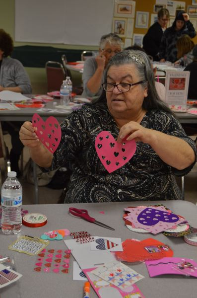 SPOTLIGHT PHOTO: COURTNEY VAUGHN - Sharon Evinger of Scappoose uses paper hearts to make valentine cards that will be given to veterans as a way to show appreciation for their service. Evinger is a volunteer with Columbia County RSVP.