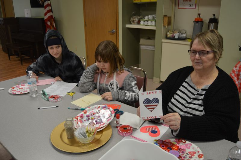 SPOTLIGHT PHOTO: COURTNEY VAUGHN - Betty Stuber (far right) shows off a card her granddaughter made during the Valentines for Vets service project day in Scappoose. To her left, Naomi Stuber, 8, (middle) and Kenzie Stuber, 13, put the finishing touches on more cards.
