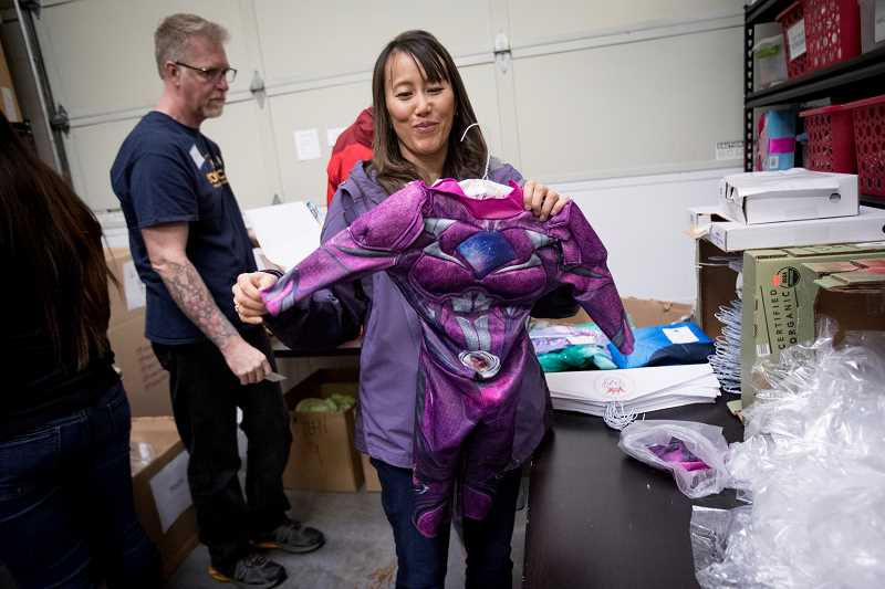 TIMES PHOTO: JAIME VALDEZ - Chelsea Nguyen who works as a home lender with Umpqua Bank, places a costume on a hanger at the Chelsea Hicks Foundation in Tigard. Nguyen volunteered along with other employees with the bank to sort through costumes for terminally ill children.