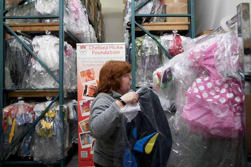TIMES PHOTO: JAIME VALDEZ - Jeannette Mayer who works in regulatory affairs with Umpqua Bank, hangs up a costume at Chelsea Hicks Foundation in Tigard.