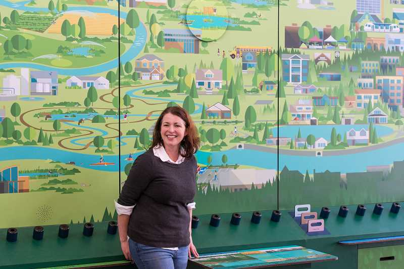 HILLSBORO TRIBUNE PHOTO: CHRISTOPHER OERTELL - Lori Prince stands before a two-story tall mural at the new Jackson Bottom Wetlands Education Center on Hillsboro Highway.