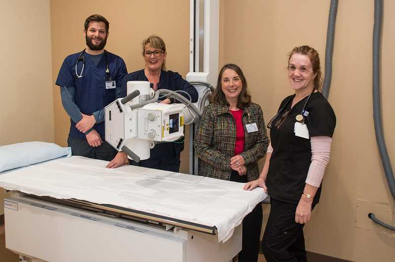 NEWS-TIMES PHOTO: CHRISTOPHER OERTELL - Physicians Assistant Matt French, Radiographer Joan Marti, Director Linda Grayson and Medical Assistant Laura Morrison pose for a photo in the X-Ray room at Adventist Health Clinic in Banks.