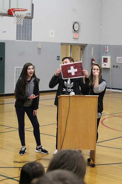 HERALD PHOTO: KRISTEN WOHLERS - Eagle Council students Jamie Mack (left) and Laela Wood (right) told jokes in between rounds of the competition. Mikey Gibson holds the sign.