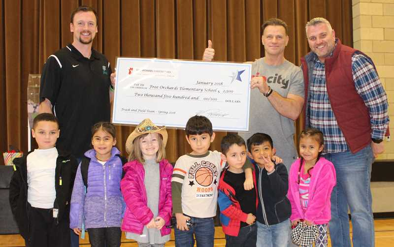 COURTESY PHOTO - Free Orchards Elementary School students accept a check for $2,500 last week, after the district received a grant to start elementary school track and field programs.