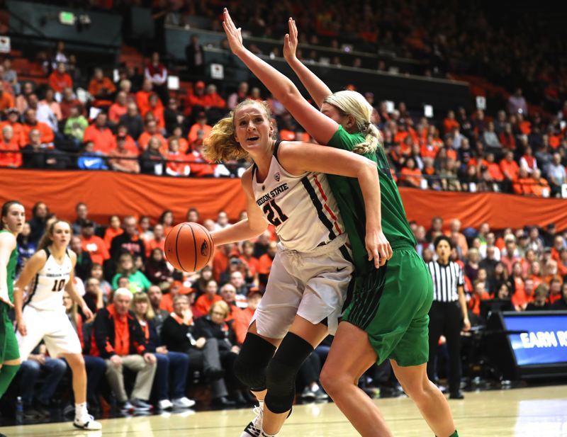 TRIBUNE PHOTO: JAIME VALDEZ - Oregon State center Marie Gulich (left) uses her arm to get around Oregon Ducks forward Mallory McGwire at Gill Coliseum.