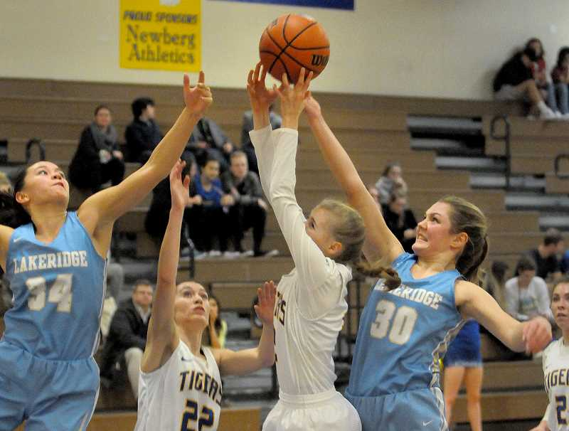 SETH GORDON - Lakeridge freshman Addie Reardon reaches over Newberg's Giselle Benetti to tap a rebound out of the paint during the Pacers' 49-40 road win at Newberg. Reardon scored 12 points.
