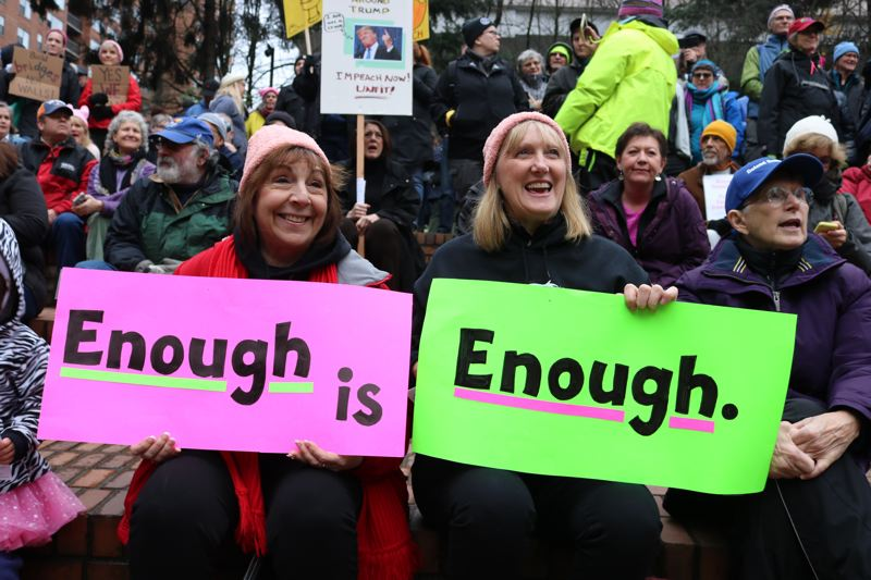TRIBUNE PHOTO: ZANE SPARLING - Two women hold signs reading 'Enough is Enough' at Terry Schrunk Plaza around 12:30 p.m. on Saturday, Jan 20 in downtown Portland.