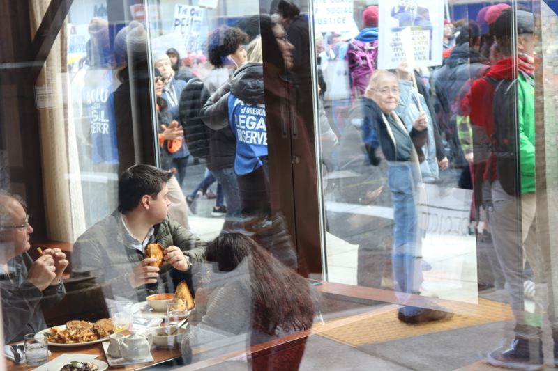 TRIBUNE PHOTO: ZANE SPARLING - Restaurant patrons watch protesters stream by on Saturday, Jan. 20 in downtown Portland.