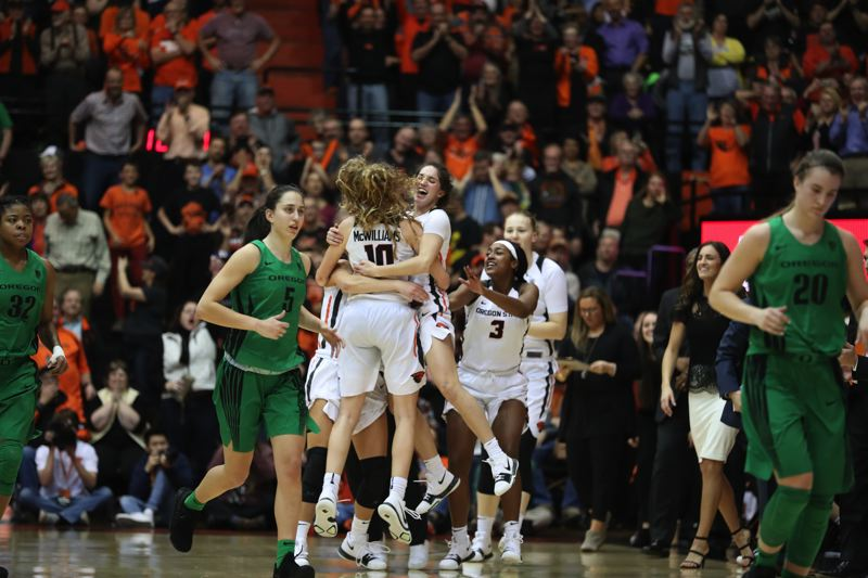 TRIBUNE PHOTO: JAIME VALDEZ - Oregon State's Katie McWilliams, who had a big four-point play late in overtime, celebrates with Oregon State teammates as Oregon players leave the floor at Corvallis.