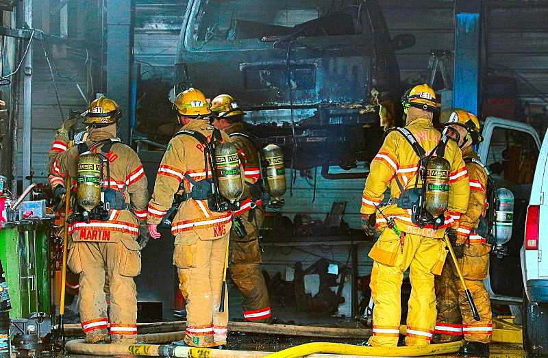 DAVID F. ASHTON - As the fire was brought under control, firefighters stood in a shop bay door opening, examining one of the charred vehicles, still on a lift.