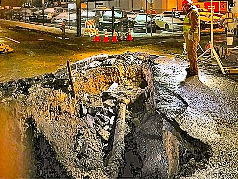 COURTESY KOIN-TV-6 NEWS - After the water to the broken pipe was shut off, and the location in the middle of S.E. 82nd was excavated, Water Bureau workers examined the ruptured cast-iron water main.